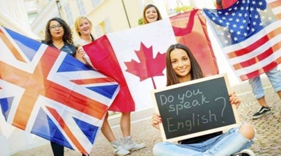 Group of English courses students holding flags of USA, Canada and USA